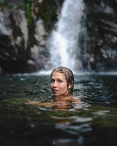 woman swimming in bish bash waterfalls looking back